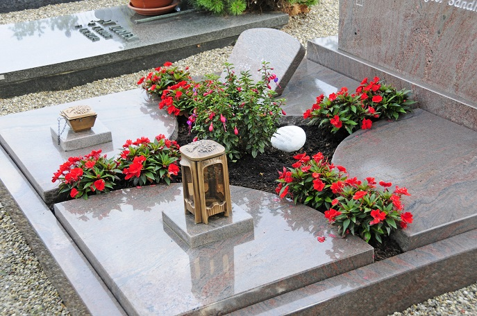 Dank der roten Blumen, die schon allein aufgrund der Blütenfarbe ein toller Blickfang sind, wird erreicht, dass diese Gedenkstätte warmherzig und offen wirkt, dass sie sich lebendig präsentiert und zeigt, dass hier an die geliebten Menschen gedacht wird. (#13)