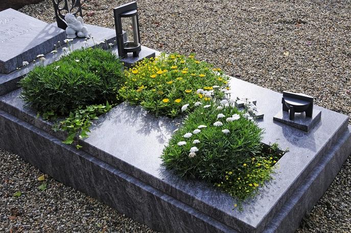 Bei dem gezeigten Beispiel wurde auf eher krautige Blumen gesetzt, die mit üppigem Grün und kleinen Blüten bestechen. Dazu kommen Kerzen und eine kleine Engelsfigur zur Auflockerung.(#16)