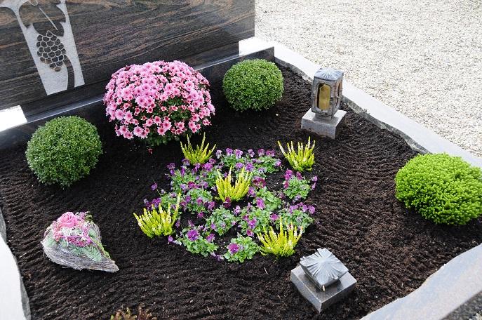 Hier ist es die Pflanze direkt vor dem Grabmal, die zum Blickfang wird. Kombiniert werden die Bepflanzungen mit Kerzenhaltern und Grabfiguren als Dekoration. (#17)