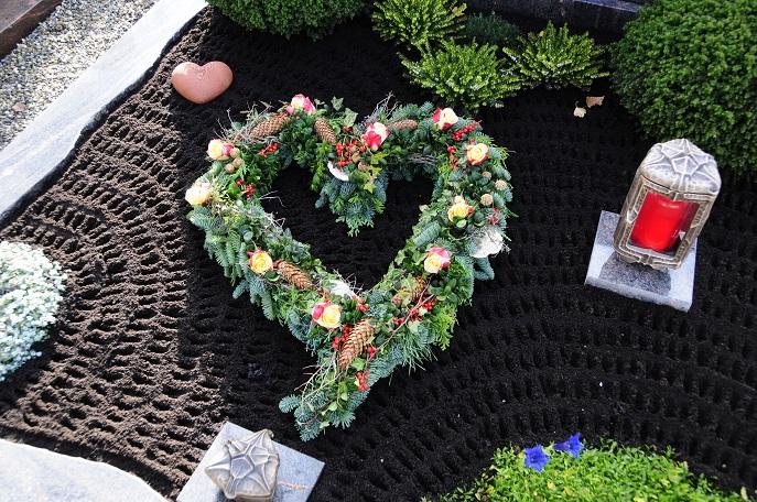 Eine Kerze sowie kleine Figuren schmücken das Grab, ein Herz aus Zweigen und Blüten bringt die Gefühle gegenüber dem Verstorbenen zum Ausdruck. (#05)