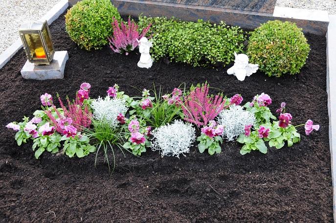 Blumen kombiniert mit langblättrigen Gräsern, kleine Deko-Figuren und die Kerze, die dem Verstorbenen das Licht weisen soll, können sehr gut nebeneinander gebracht werden.(#01)