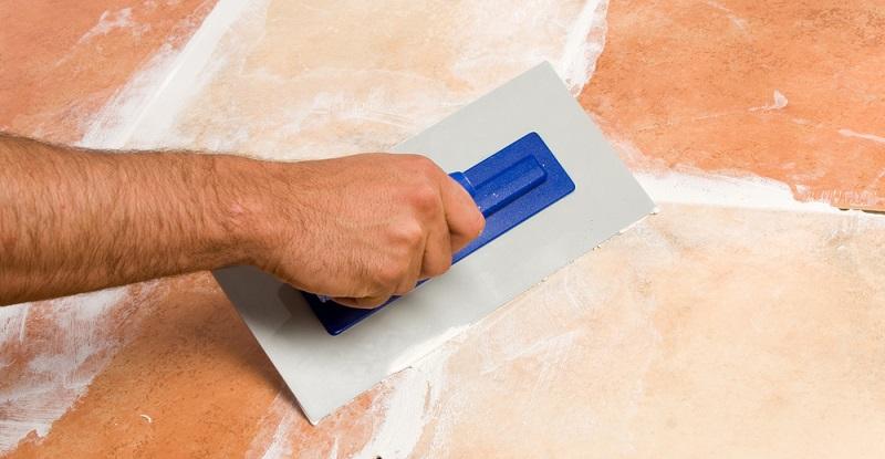 Der Fugenmörtel wird dafür mit dem Fugengummi in die Fugen gestrichen, wobei der Fugenmörtel an der Wand deutlich weniger flüssig als auf dem Boden ist.