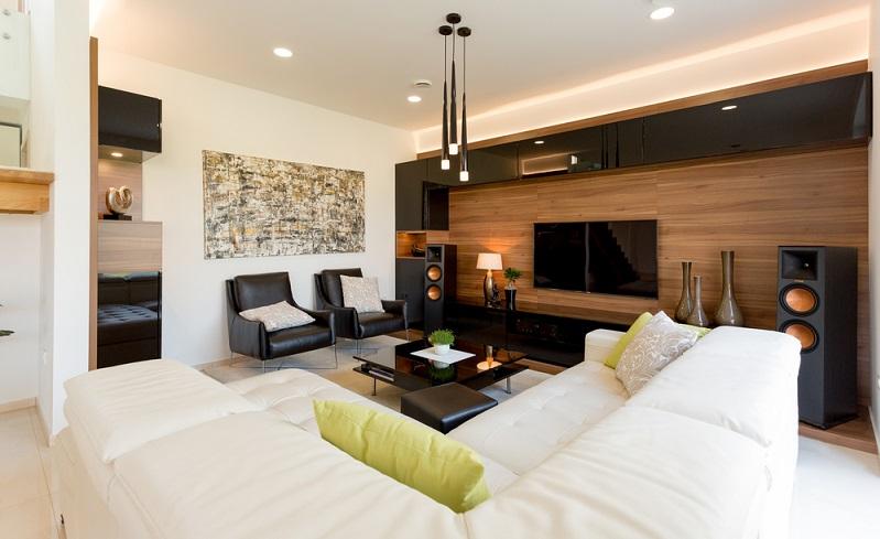 Deckenlampen, Spots und Stehlampen ergänzen sich in diesem Raum perfekt und werden durch die Verkleidung der Wohnwand in ihrer Wirkung noch unterstrichen.  (Foto: Shutterstock- JRP Studio)